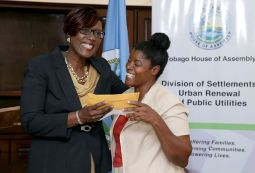 Administrator of the Division of Settlements, Urban Renewal and Public Utilities Joan Hannibal-Phillips presents a cheque to Erica Des Vignes.