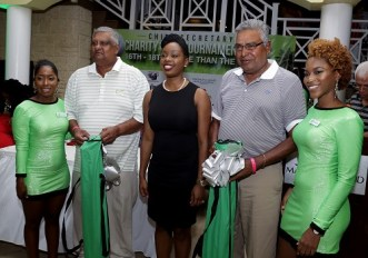 Secretary of Tourism, Culture and Transportation Councillor Nadine Stewart-Phillips, along with with golfers Steve Mahabir and Durham Quashie, who placed third. Bmobile girls Leah Richards, left and Vanesha Johnson assisted in the prize distribution.