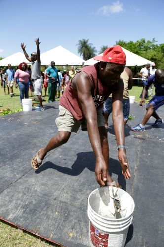 John Melville throws a crab in the bucket as he competes during the crab catching event.