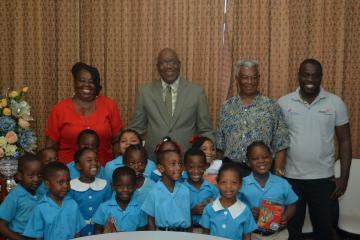 Chief Secretary Kelvin Charles, second from left, back row, stands with ABC Nursery School students, and other members of the visiting school. To his left is principal Noreen Gray-Hamilton.