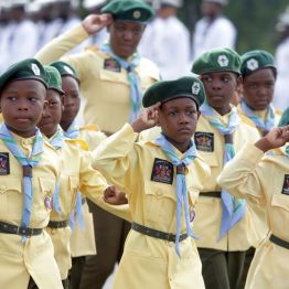 The Boy Scouts salute as they march on.