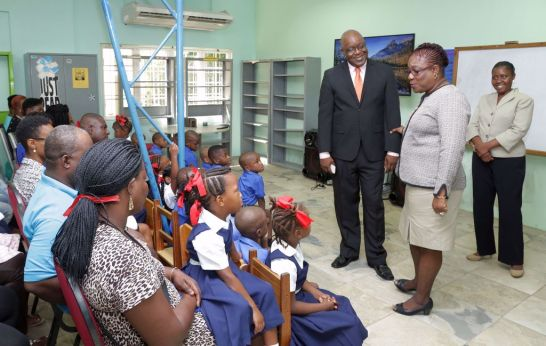 Chief Secretary Kelvin Charles visits students at Black Rock Government school where he is introduced by teacher Mrs. Moore-Carrington. Assistant Secretary in the Division of Education, Innovation, and Energy Marisha Osmond looks on.