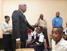 A pupil from Plymouth Anglican school is all smiles on greeting Chief Secretary Kelvin Charles during his visit.
