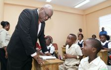 Chief Secretary Kelvin Charles leans in closer to listen to pupils of the Plymouth Anglican Primary school during his visit there on Monday.