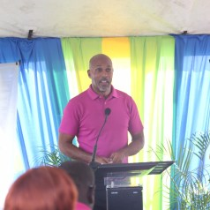 Secretary for Sport and Youth affairs Jomo Pitt, Assemblyman Jomo Pitt address the crowd at the opening of the new Signal Hill Youth Centre. Looking on is Youth Auxillary Officer, Nathalia Joseph.