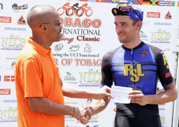 Division of Tourism, Culture and Transportation Marketing Officer Nigel Wilson, left, presents Denmark's Peter Schulting with the winner's prize after the Tour of Tobago.