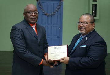 THA Chief Secretary Kelvin Charles, left, receives an appreciation award on behalf of the chairman of the board of directors of Habitat for Humanity Trinidad and Tobago, Derwin Howell.