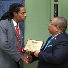 Moriah Village Council president Kevon Thomas, left, receives an appreciation award from chairman of the board of directors of Habitat for Humanity Trinidad and Tobago Derwin Howell.