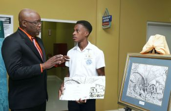 THA Chief Secretary Kelvin Charles has a chat with the winner of the 2017 art competition Shakir James of Scarborough Secondary School with his charcoal piece the 'Arnos Vale Water Wheel.'