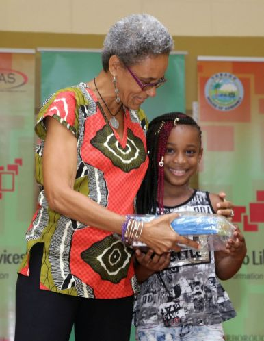 Library assistant Althea Perkins presents a prize to Anaiya Caesar who placed third in the 5-8 year old age group. Caesar read 34 books.