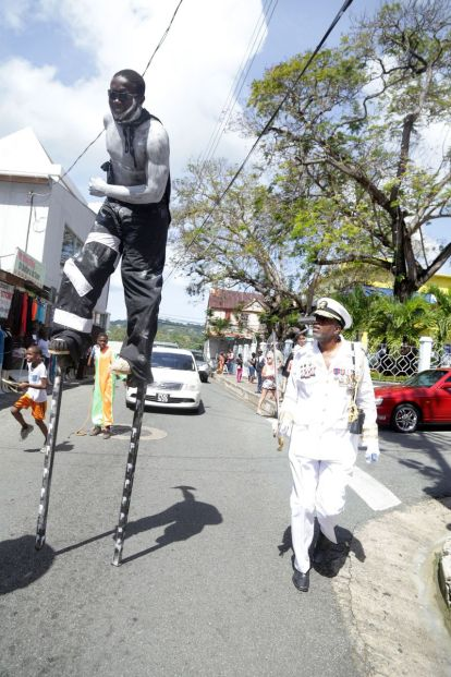 A moko jumbie walks the streets of uptown Scarborough as Chairman of the Tobago Festivals Commission George Leacock looks on.