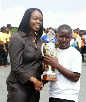 Secretary of Tourism, Culture and Transportation Councillor Nadine Stewart-Phillips presents Akel Quashie of Parlatuvier Anglican Primary school with the winners trophy.