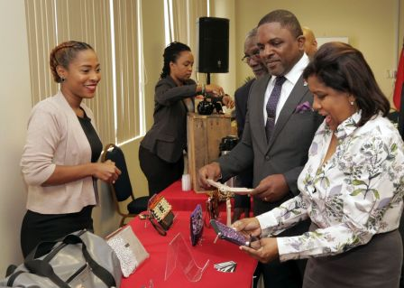 Trade Minister Paula Gopee-Scoon shows her enthusiasm while looking at an Osanie Designs bag as its creator Avien Thomas stands at a display table of products made by Tobago small business manufacturers. Looking on is Finance Secretary Joel Jack.