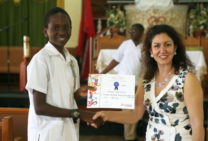 Adjudicator Belinda Michael of the UK, presents Bishops student Michael Paria with the certificate for his school as winners of the boys school choir under 15.