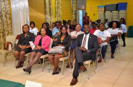 Assistant Secretary of Community Development, Enterprise Development and Labour Shomari Hector, right, sits with attendees during the event.