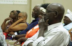 Members of the audience listen as Chief Secretary Kelvin Charles responds to a question during the meeting.