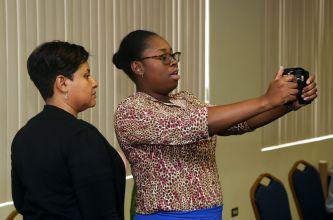 Dietary technician Allison Quintero-Constantine, left, helps a staff member perform a body mass index test.