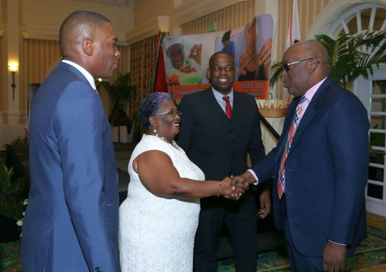 Chief Secretary Kelvin Charles is greeted by YTEPP Chairman Thora Best, as Minister in the Ministry of Education Dr Lovell Francis, second from right, and YTEPP's Chief Executive Officer Nigel Forgenie look on.