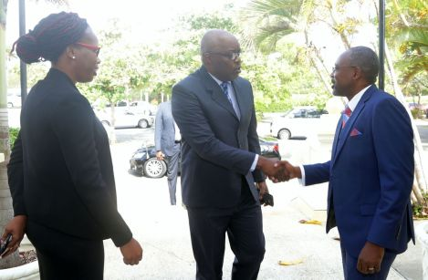 Financial Intelligence Unit Acting Director Nigel Stoddard, right, greets Chief Secretary Kelvin Charles on his arrival at the Magdalena Grand. At left is FIU's representative Avelon Perry.