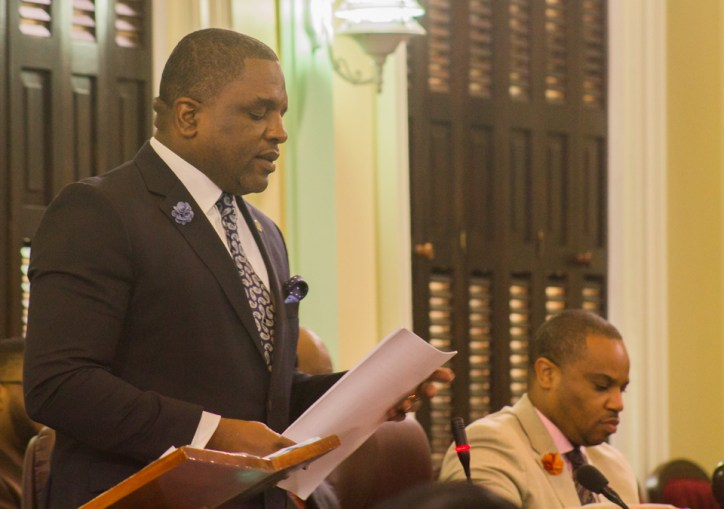 Secretary of Finance and the Economy Joel Jack presents the fiscal 2019 budget statement. Seated is Secretary of the Division of Infrastructure, Quarries and the Environment Kwesi Des Vignes.