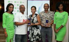 Executive Manager of the Mt Irvine Bay Resort Jacqueline Yorke-Westcott presents third placed finishers Bill Ramrattan, right, and Earnest De Gannes with their prize as bMobile girls Kyshauna Warner, left, and Lisette Brooks look on.