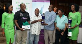 Tournament winners Carlos Baynes, left, and Akash Ragbir receive their trophy from Chief Secretary Kelvin Charles, as Caribbean Airlines' Tobago Manager Rodney Craig, second from left, and bMobile girl Kyshauna Warner, left, and Lisette Brooks look on.