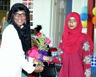 Catherine Anthony-Charles, wife of Chief Secretary Kelvin Charles, receives a gift from Halima Ali.