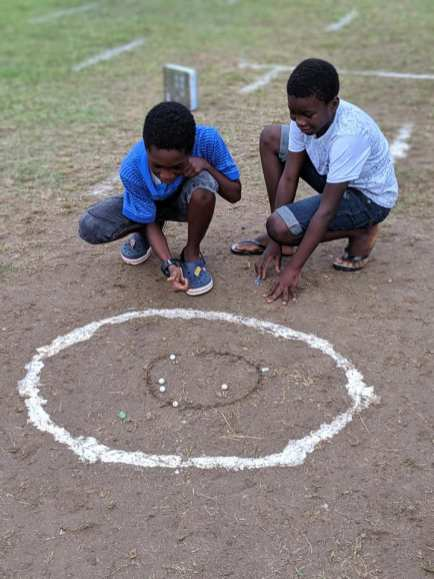 Youngsters pitch marble.