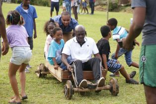 Secretary of the Division of Infrastructure, Quarries, and the Environment Kwesi Des Vignes pushes a boxcart.