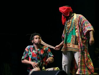 Tour guide Benny (Kevin Henry) turns obeah man as he beats Leonard (Daniel Perreira) with a cocoyea broom in the opening night production.