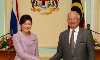 Thailand Prime Minister Yingluck Shinawatra (L) shakes hands with her Malaysian counterpart Najib Razak