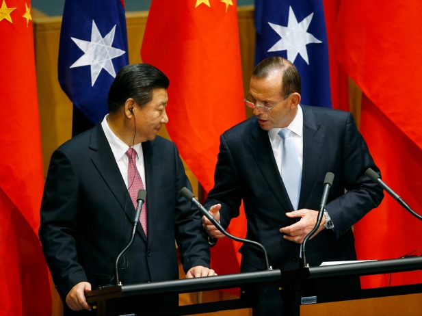 China s President Xi Jinping (L) listens as Australia's Prime Minister Tony Abbott speaks after a signing ceremony for a free trade deal at Parliament House in Canberra November 17, 2014.