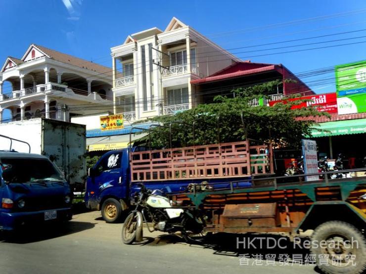 Photo: Trucks driving down a street in Phnom Penh.