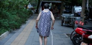An elderly woman walks with a stick along a street in downtown Beijing, China 30 July, 2019 (Photo: Reuters/Lee).