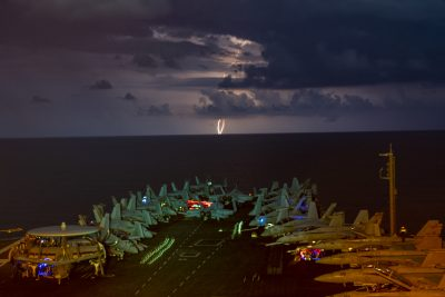 Lightning flashes over the aircraft carrier USS Nimitz (CVN 68) as it transits the South China Sea, 4 July, 2020. (Reuters/John Philip Wagner, Jr.).