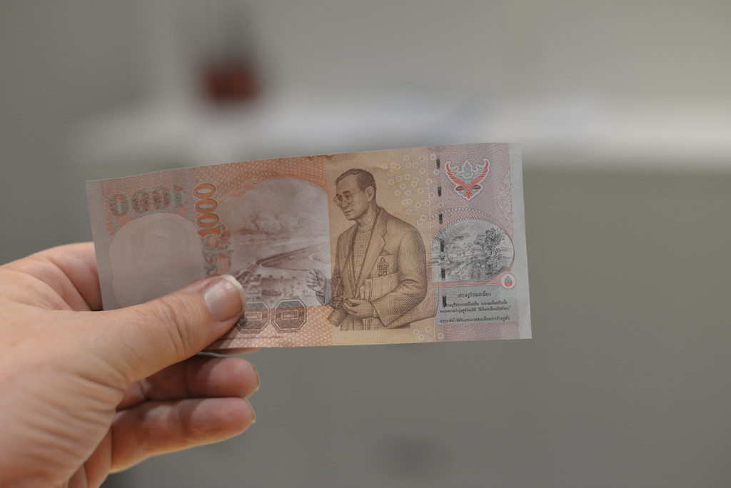 The back of a 1000 Baht banknote, with the image of King Rama IX, H.M. Bhumibol Adulyadej
