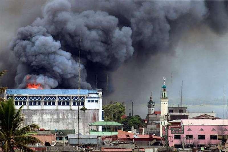 A building in Marawi is set ablaze by air strikes