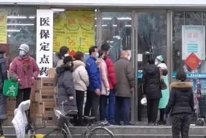 People lining up outside of a drug store to buy masks during the Wuhan coronavirus outbreak in Wuhan, China