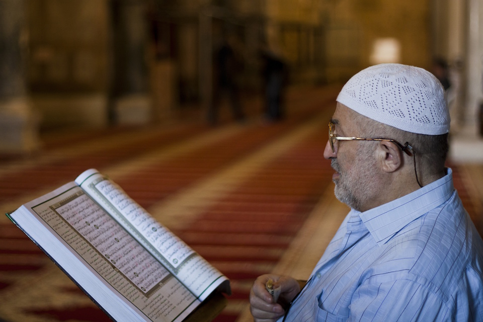 Muslim man reading the Quran in a mosqu