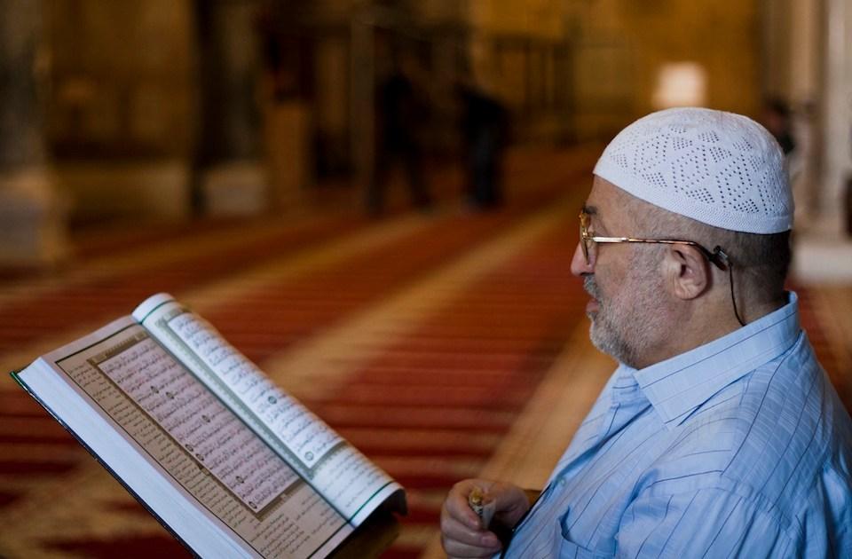 Muslim man reading the Quran in a mosqu