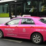 Colorful pink taxi and public bus in Bangkok