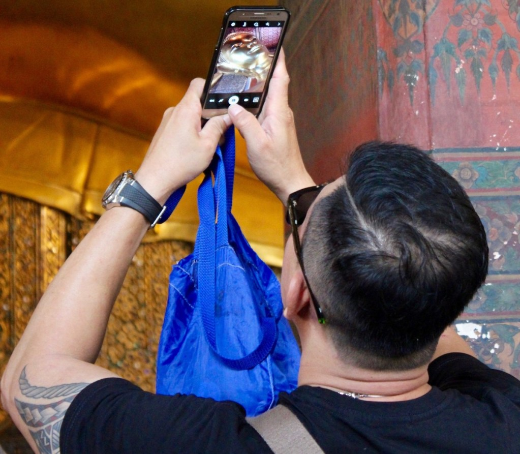 Asian tourist taking a photo at a Buddhist temple