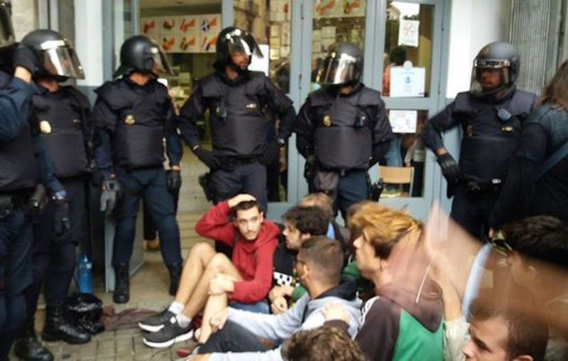 Spanish police officers charge against peaceful voters in Catalonia