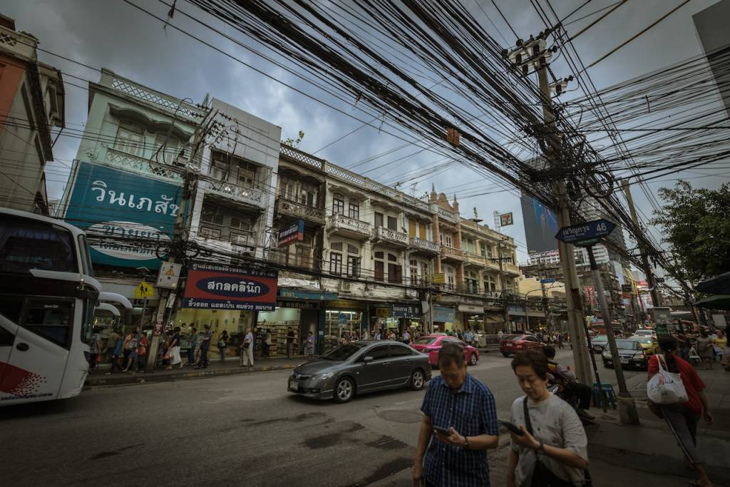 Street in Bangkok with light traffic jam and overhead power cables