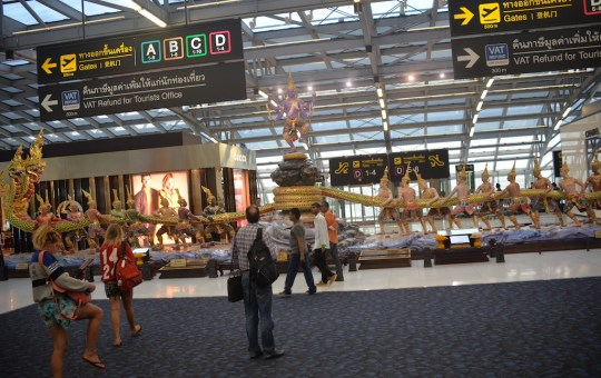 """Inside the departures terminal at Suvarnabhumi International Airport in Bangkok. Gates and VAT Refund signs and the statue of the Hindu gods known as """"stirring the ocean"""""""