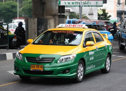 Toyota Saloon sedan taxi driving on the road in Bangkok