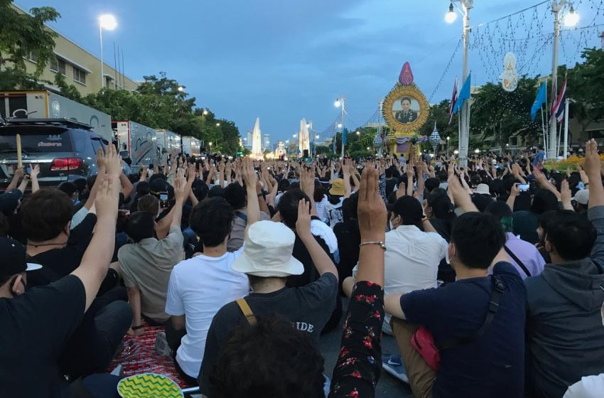Protesters displaying three-finger salute in front of Democracy Monument in Bangkok