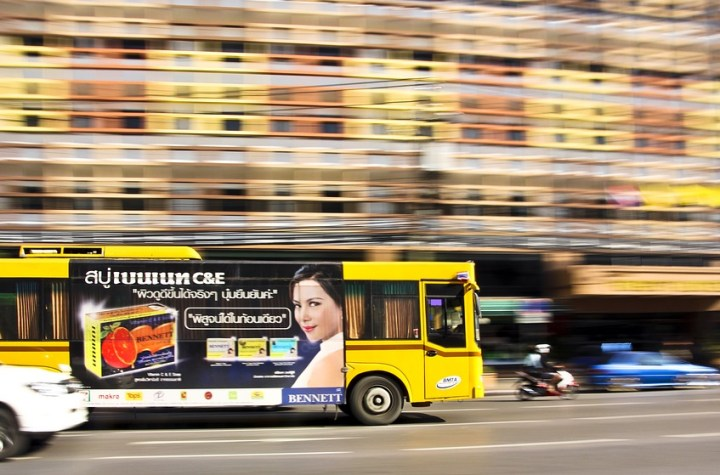 A yellow bus with ads in Bangkok