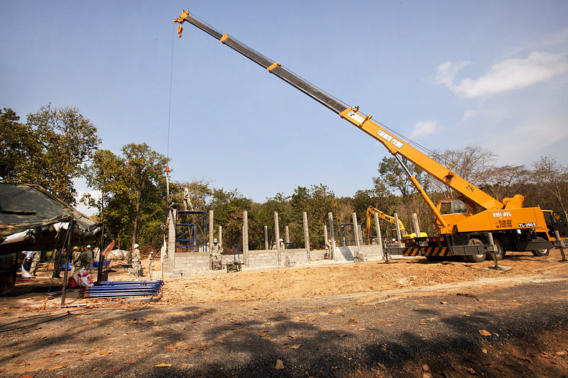 A Thai soldier operates a crane to lower a metal truss onto a multipurpose building during exercise Cobra Gold 2012