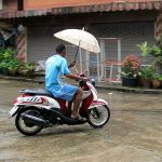 Thai man riding a Yamaha Mio Fino Sport scooter and holding an umbrella